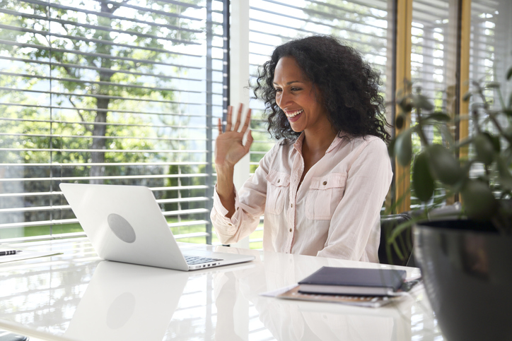 Woman waving at computer during video call