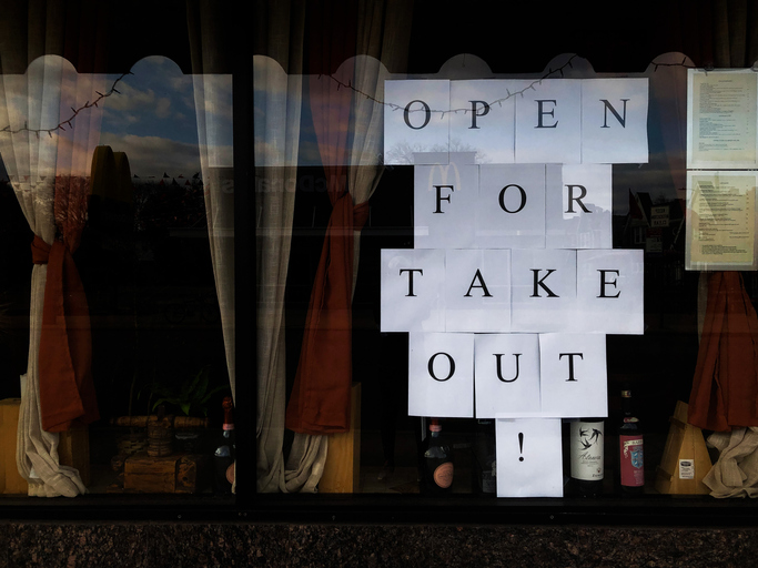 Restaurant window with sign: Open for Takeout!