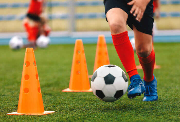 Legs of a young soccer player shown dribbling ball between orange cones at practice.