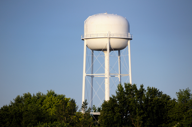 White water tower with trees below it