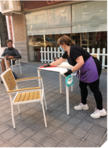 A restaurant employee wipes down an outside dining table.