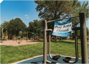 Play Area Closed sign on playground equipment.