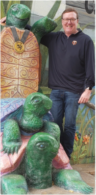 Mike Mornson posing with a turtle statue