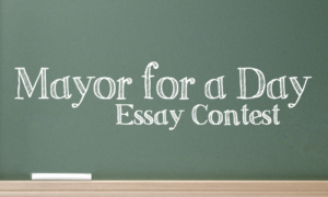 The words Mayor for a Day Essay Contest are written on a green chalkboard in chalk.