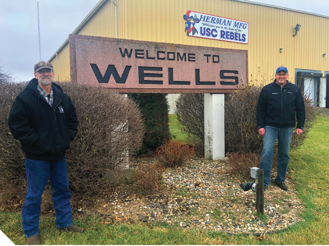 "Wells Council Member John Herman, left, and Wells EDA President Brad Heggen stand by sign that says ""Welcome to Wells."""