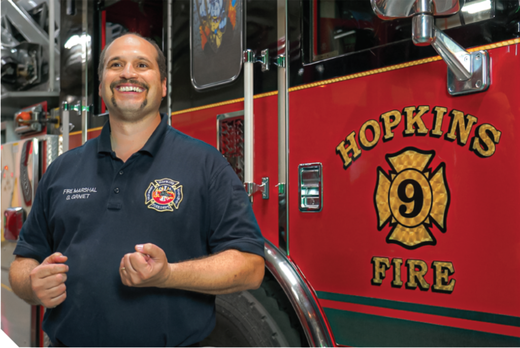 Hopkins Fire Marshall Garrett Grniet stands next to a Hopkins firetruck.
