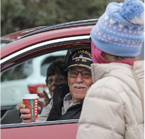 A volunteer serves coffee to a veteran during Plymouth's drive-thru veterans breakfast.