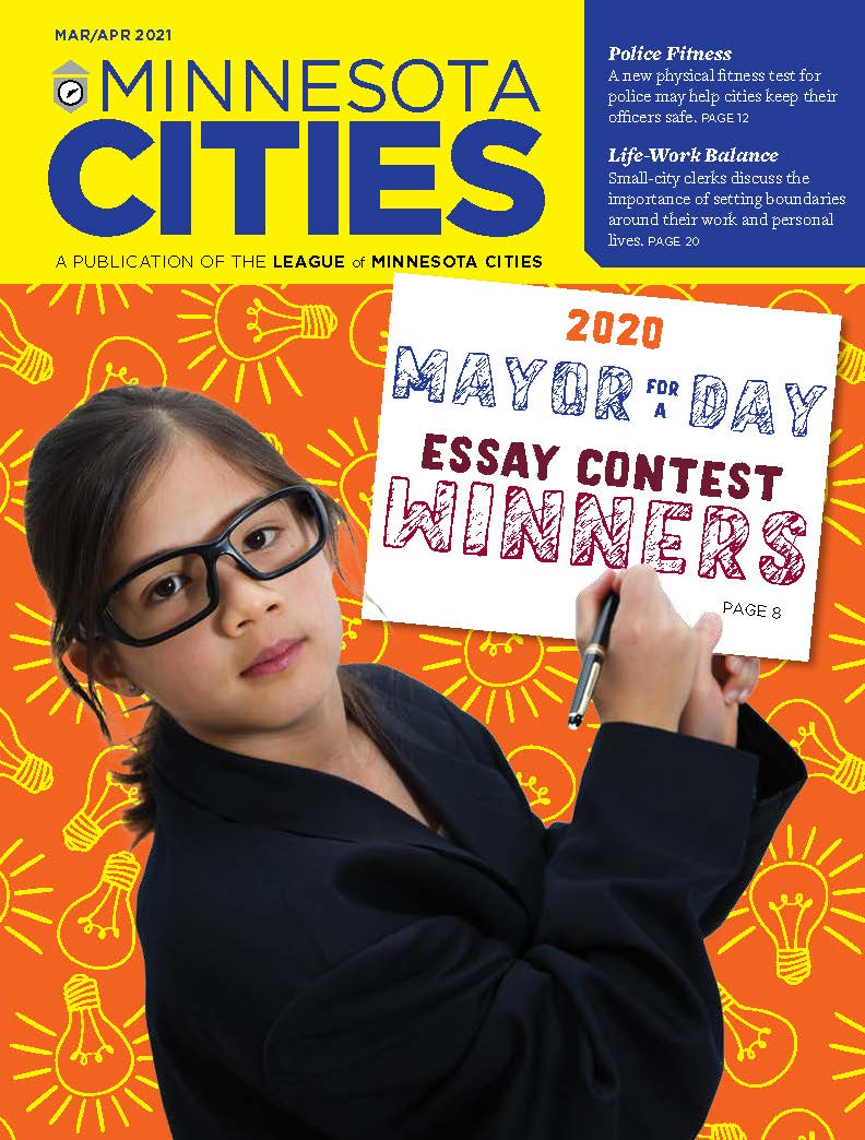 MN Cities magazine Mar Apr 2021 cover: A young girl holds up a pen and sign that says 2020 Mayor for a Day Essay Contest Winners