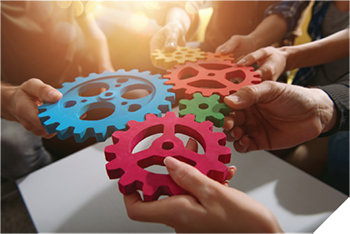 Hands holding colorful gears.